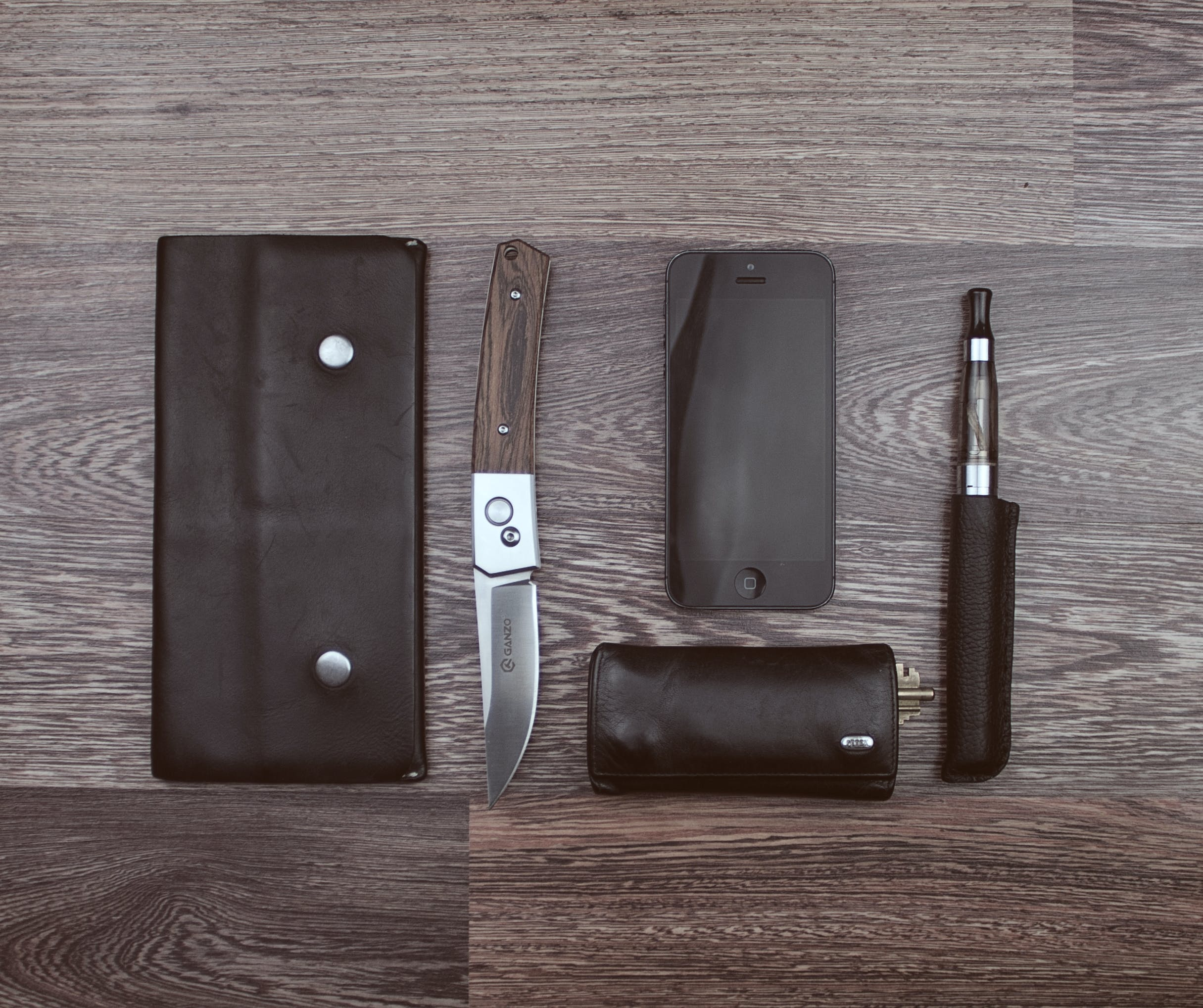 Brown Knife, Black Iphone 5 and Black Vaporizer Pen on Brown Wooden Surface