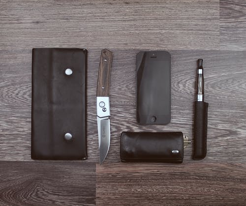 Coltello Marrone, Iphone 5 Nero E Penna Vaporizzatore Nera Su Superficie In Legno Marrone