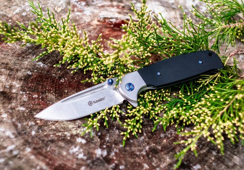 Silver and Black Folding Knife on Green Grass