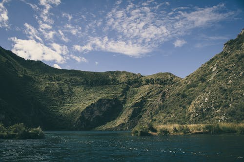 Landscape Photography of Hill Near Body of Water