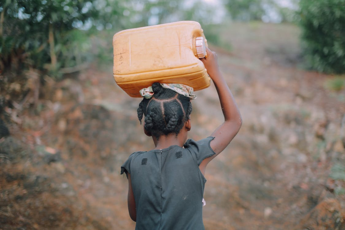 Photo of Child Carrying Jug