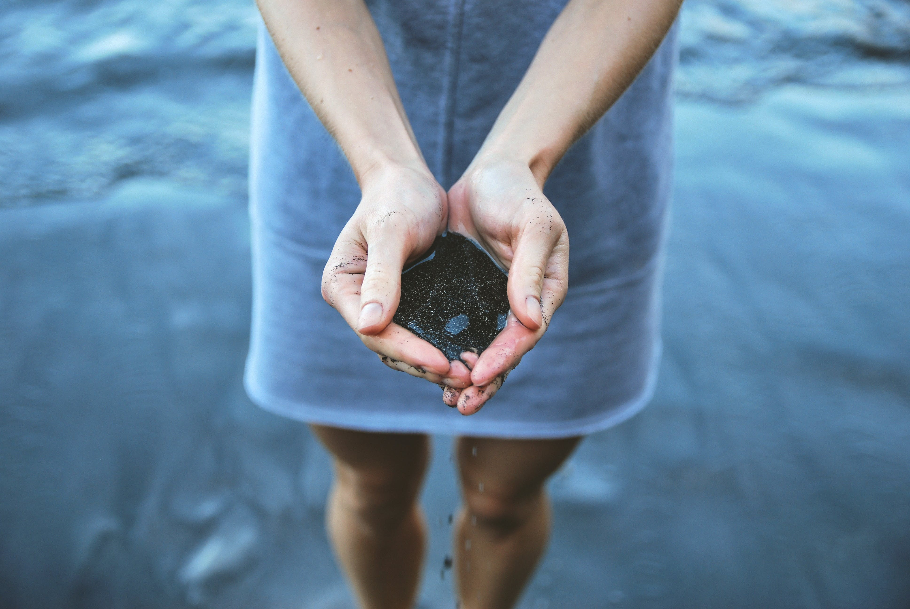 Woman Holding Black Sand on Seashore Du