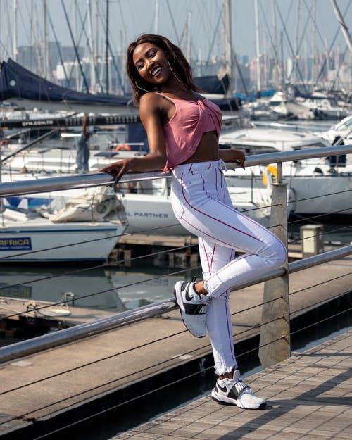 Photo of Smiling Woman in Pink Crop Top Leaning on Metal Railing by Harbor