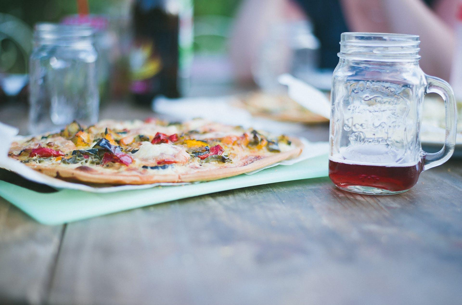 Pizza on Green Chopping Board Near Two Clear Glass Mugs