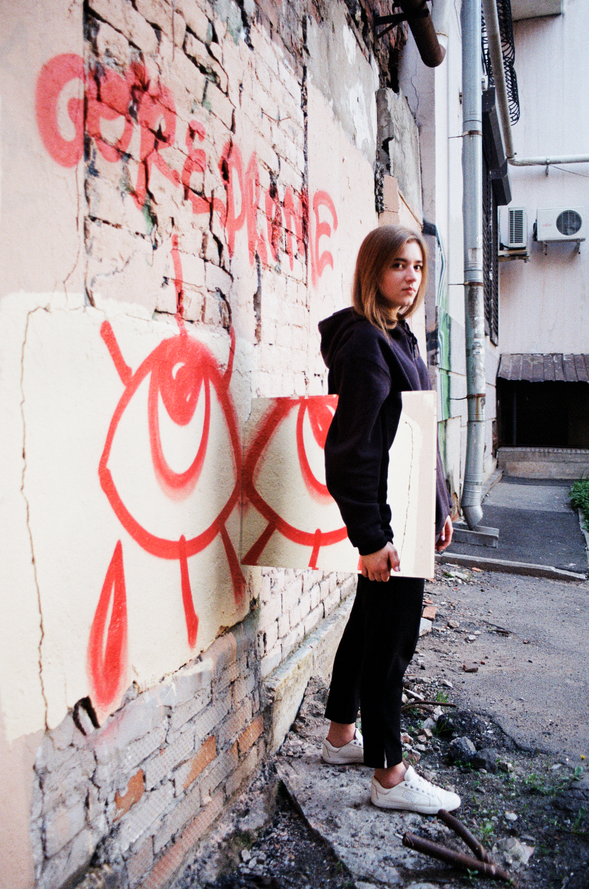 Photo of Woman Wearing a Hoodie and Black Pants Standing Near Wall