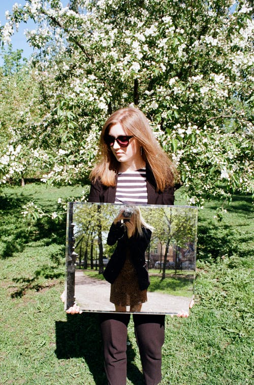 woman holding a mirror outdoors