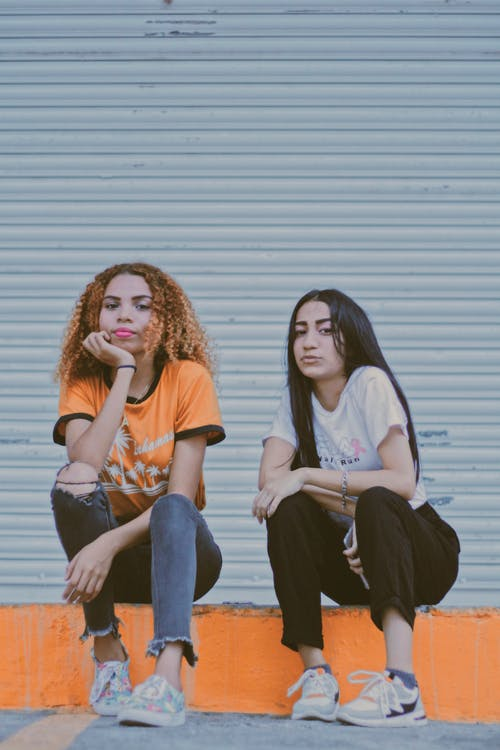 Two Woman Sitting on Orange Concrete Pathway
