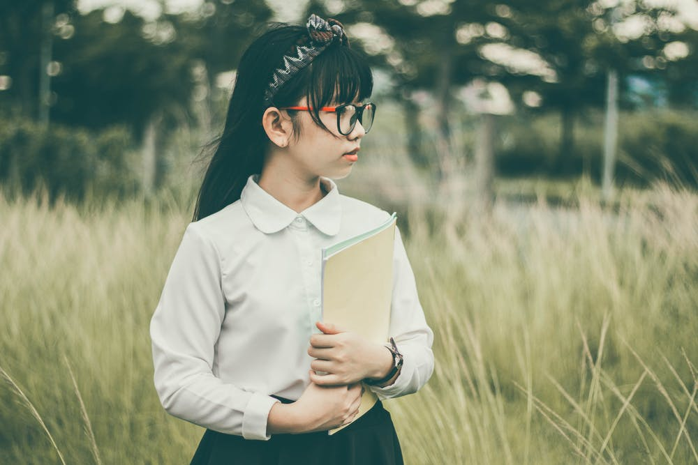 Girl holding a brown folder. | Photo: Pexels