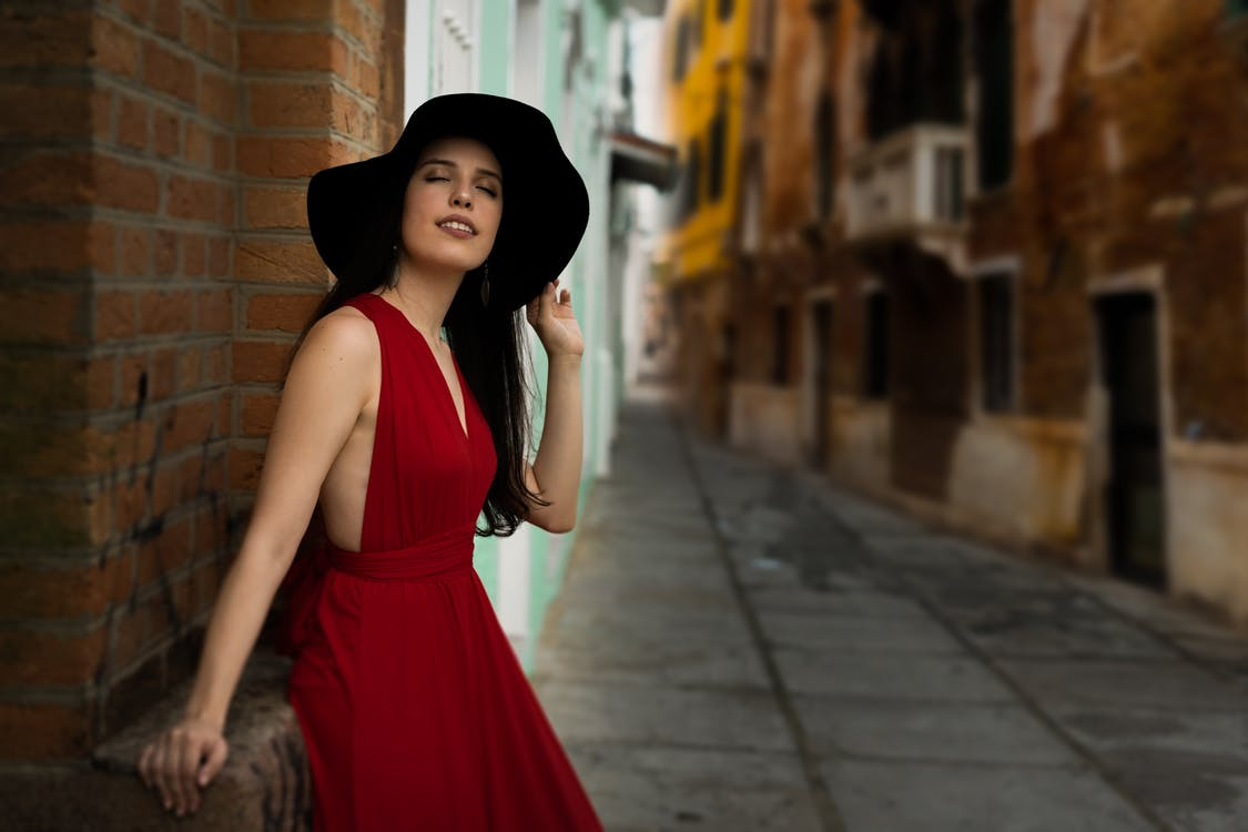 Photo of Woman With Her Eyes Closed Wearing a Red Dress and Black Hat Leaning on Red Brick Wall in Alley