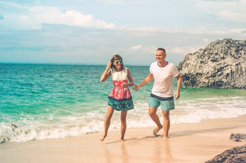 Photo of Laughing Couple Walking by the Beach