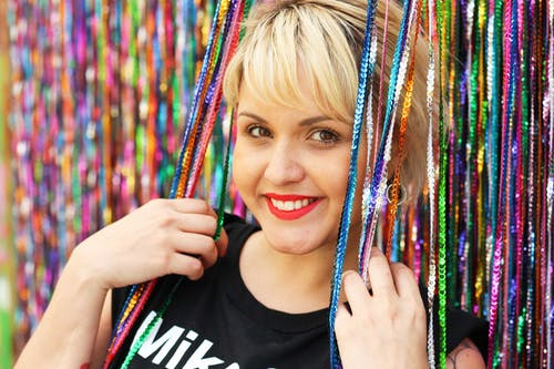 Woman Leaning Against Wall Full of Sequin Ropes