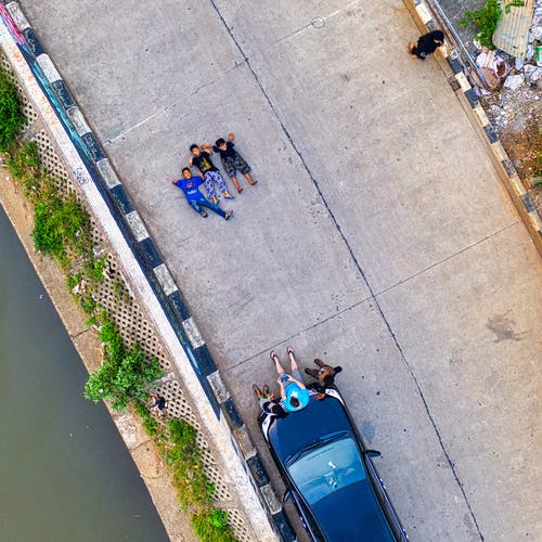 Aerial Photography Unknown People Lying on Road