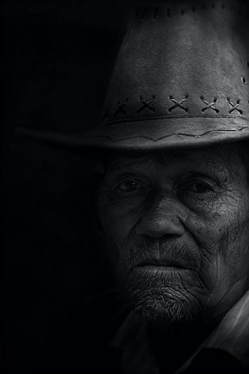 Monochrome Photo of Man Wearing Cowboy Hat