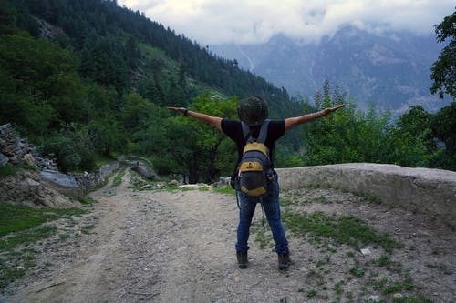 Person Standing and Raising Both Hands Near Mountain