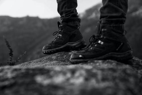 Monochrome Photo of Person Wearing Black Shoes