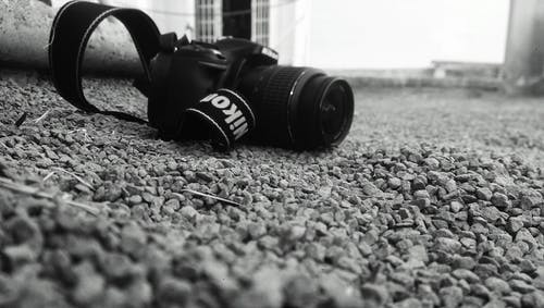 Nikon Dslr Camera Placed on Ground With Rubble Grayscale Photo