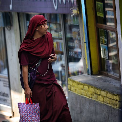 Man With Red Hijab Walking Past Store