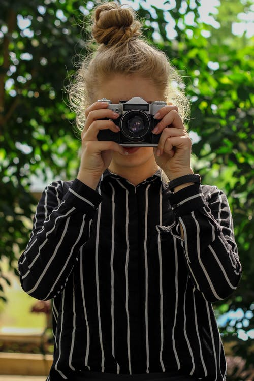 Portrait Photo of Woman in Black and White Striped Top Taking Photo