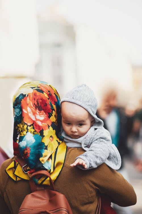 Woman Carrying Baby While Walking on the Street