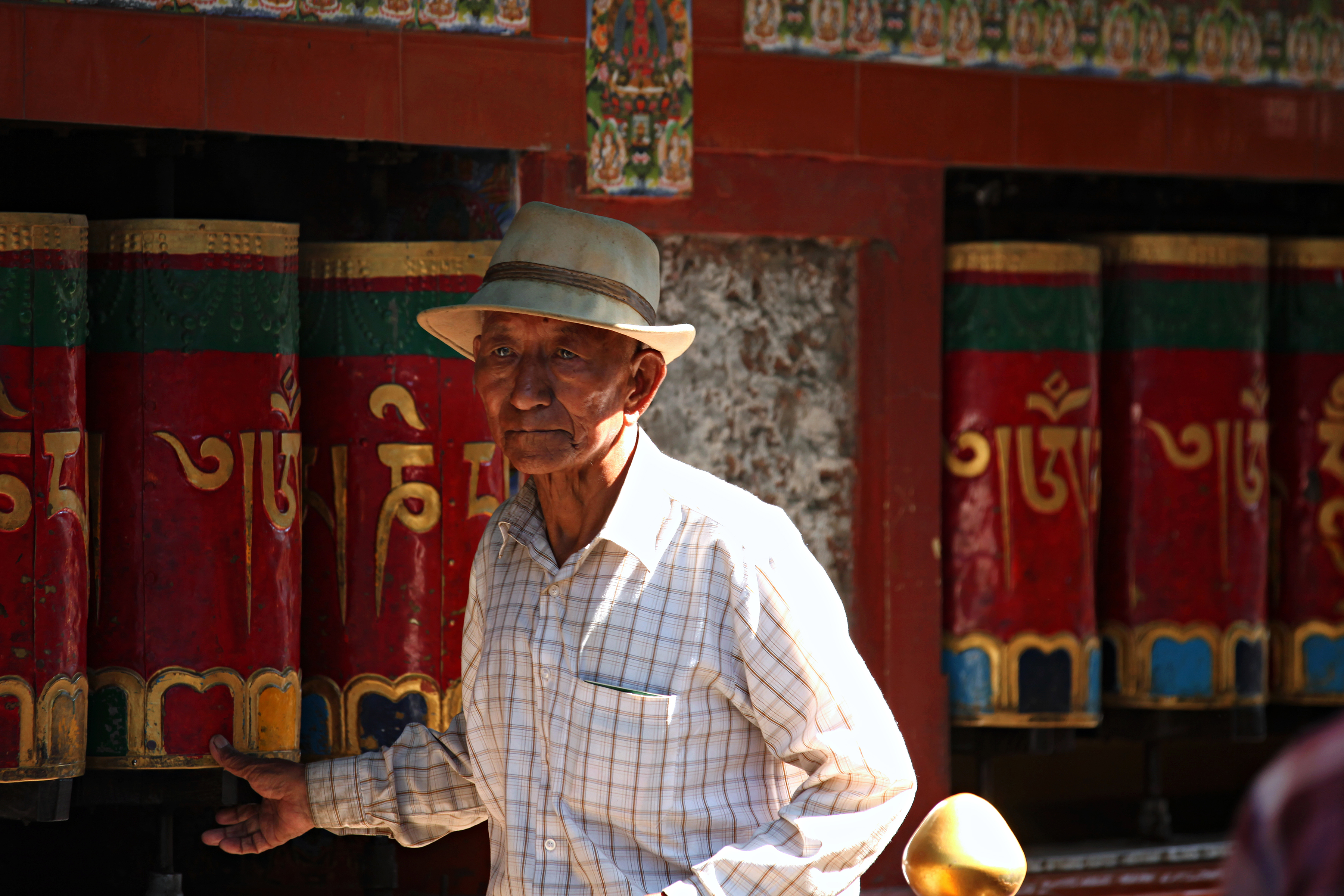 Man Standing Near Red Wooden Wall