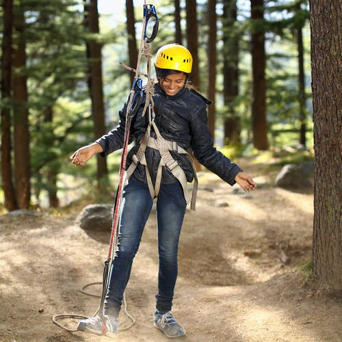 Woman Standing and Smiling While Putting Right Leg on Camping Rope Near Trees