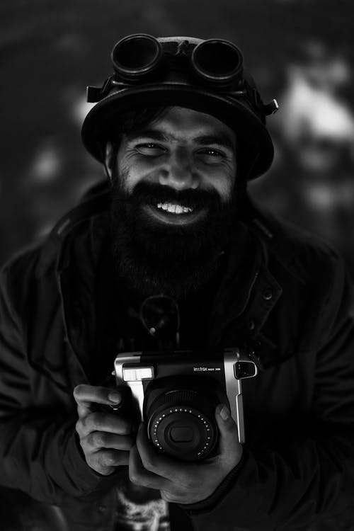 Man Smiling While Holding A Camera