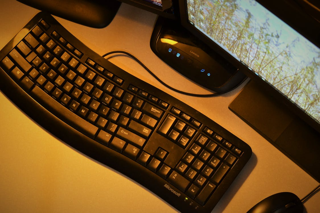 Black Corded Computer Keyboard Near Monitor