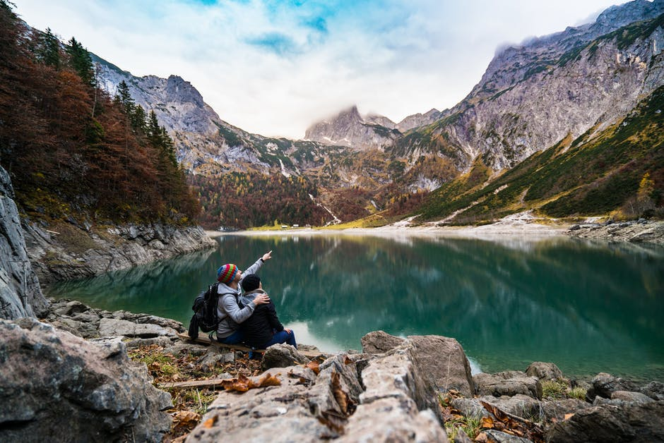 Couple Sitting on Rock Beside Lake