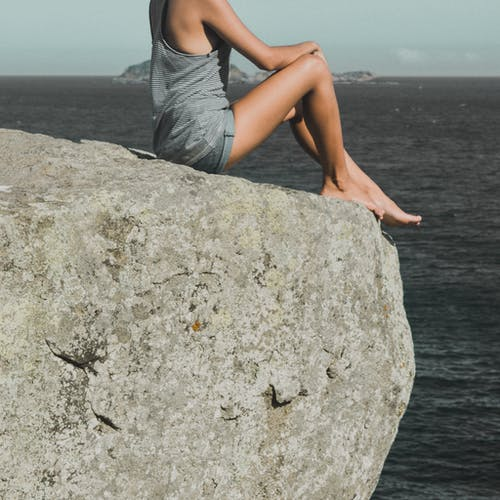 Woman Sitting on Gray Stone