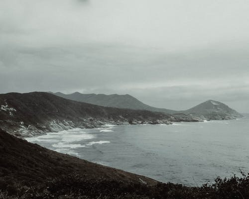 Mountain Overlooking Beach Under Grey Cloudy Sky