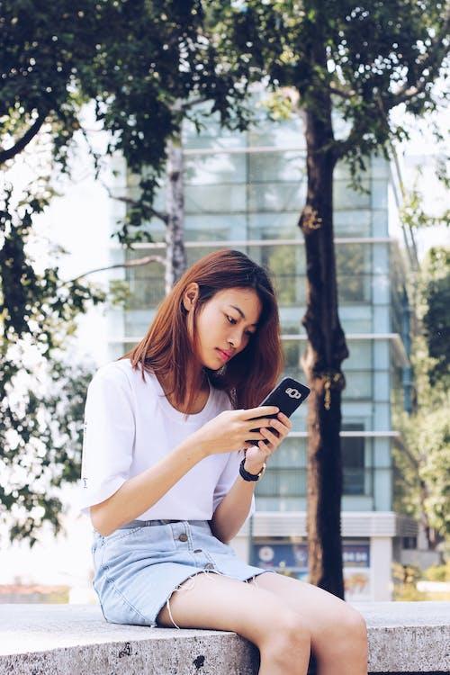 açık hava, akıllı telefon, Asyalı kadın, bakmak içeren Ücretsiz stok fotoğraf