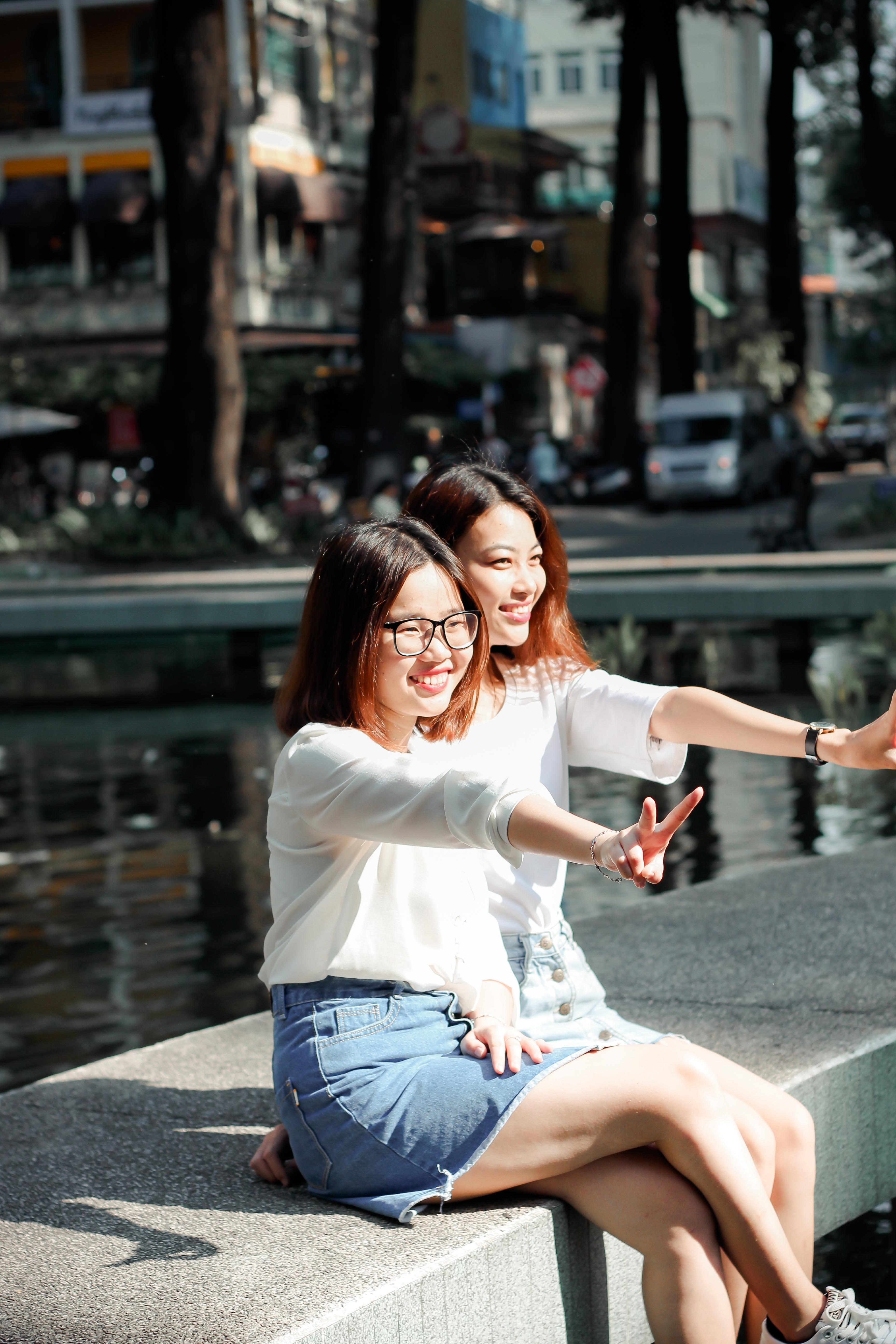 Smiling Women Sitting on Concrete Block