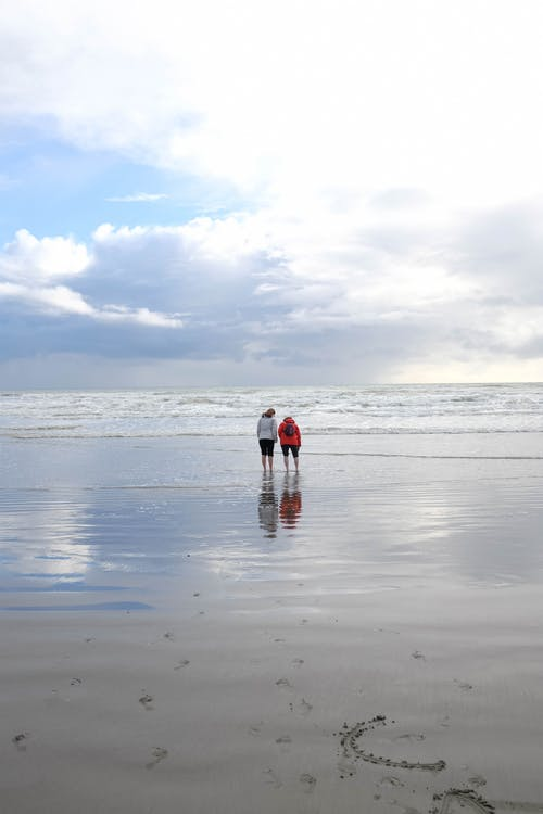 Two People Walking on Seashore