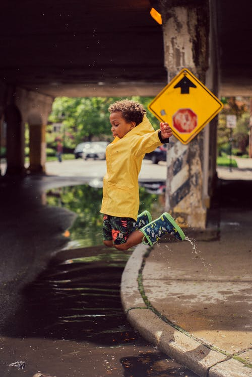Boy Jumping from Road Curb