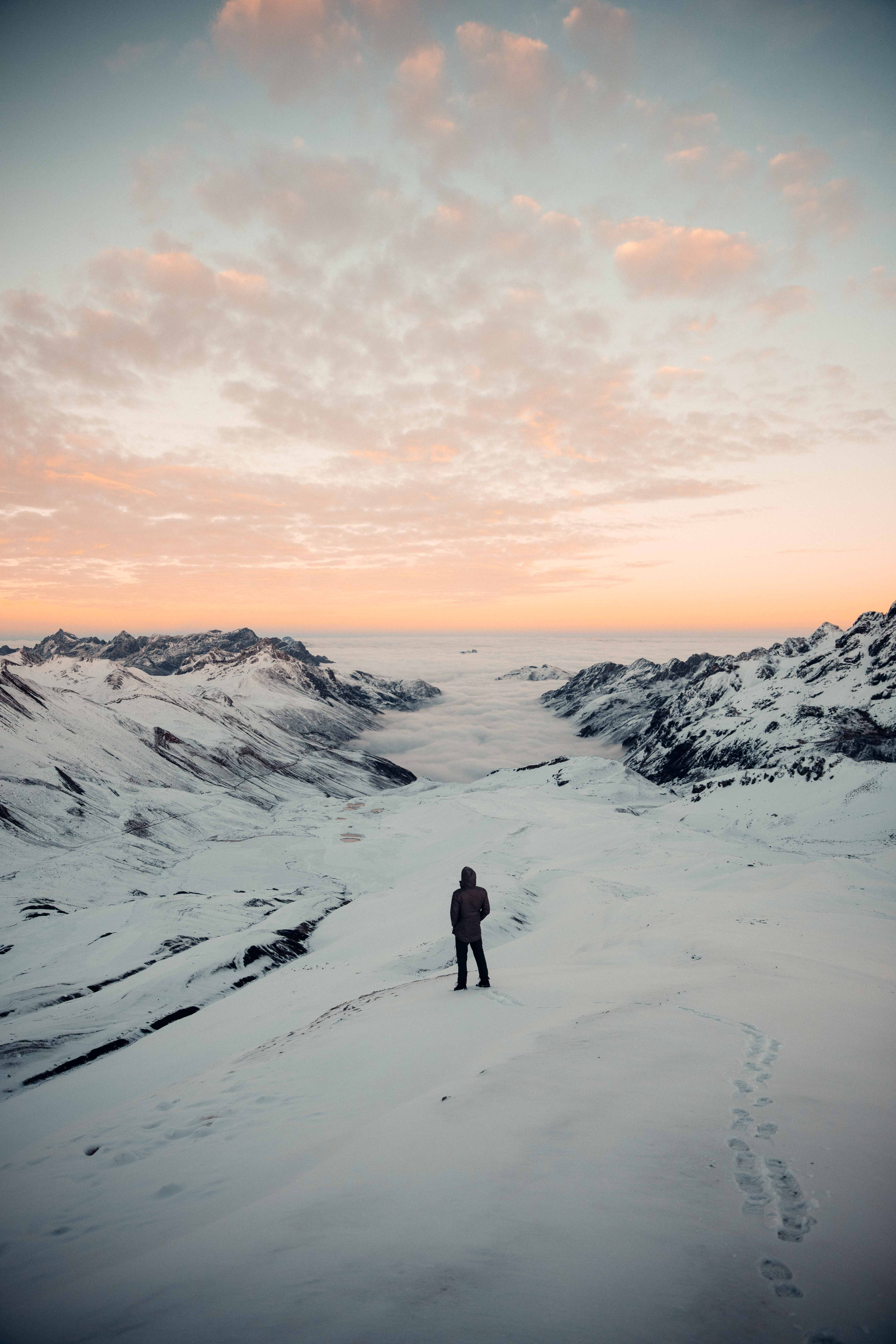 Person Standing in Snowy Field Under White and Orange Skies
