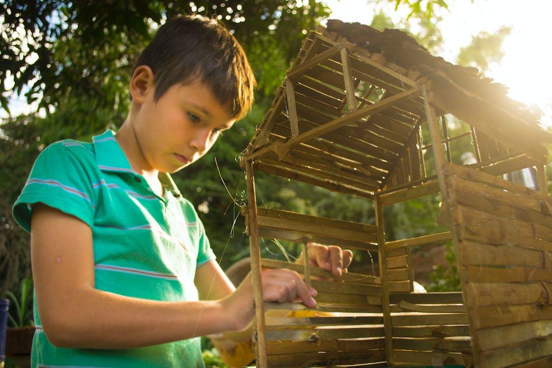 Boy Making Wooden House Miniature