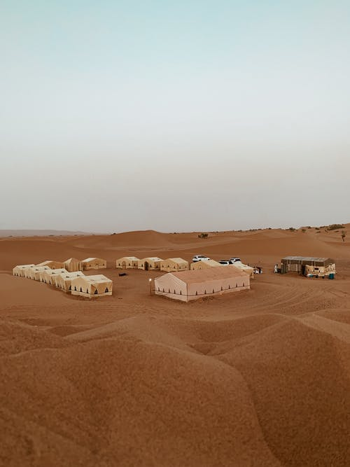 Sandy desert with dunes and cars near tents