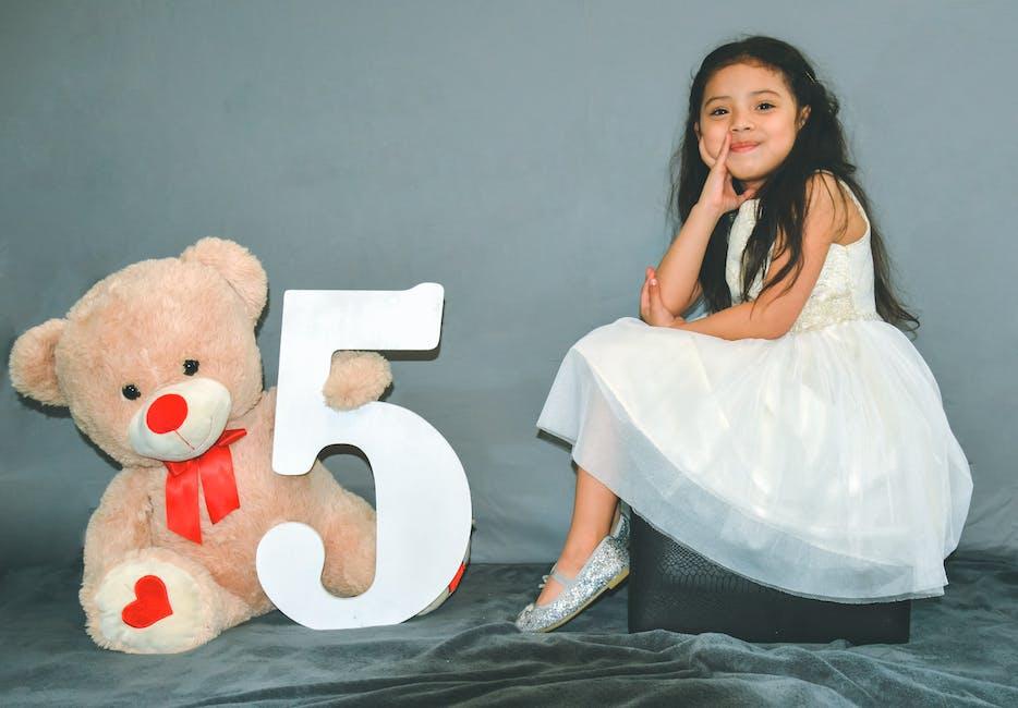 Girl sitting beside bear plush toy