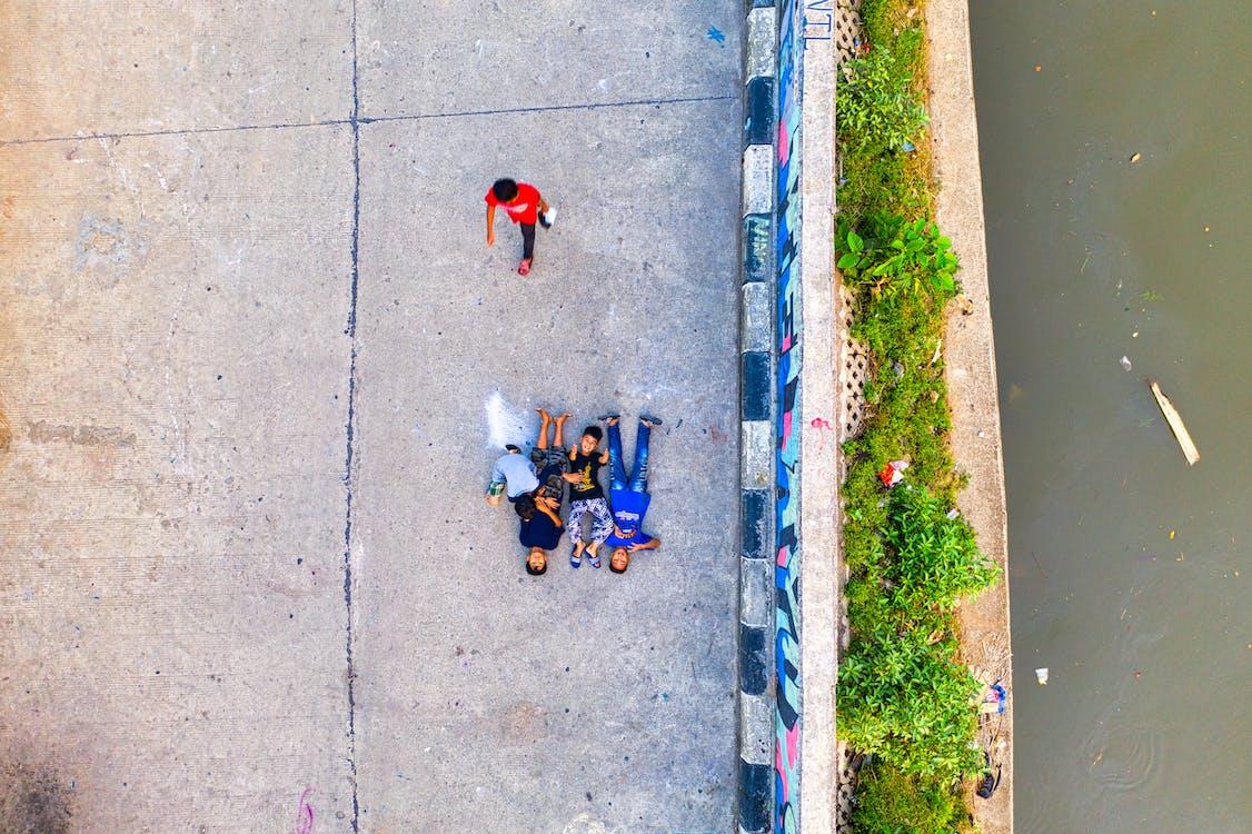 Children Lying on Road Along the River