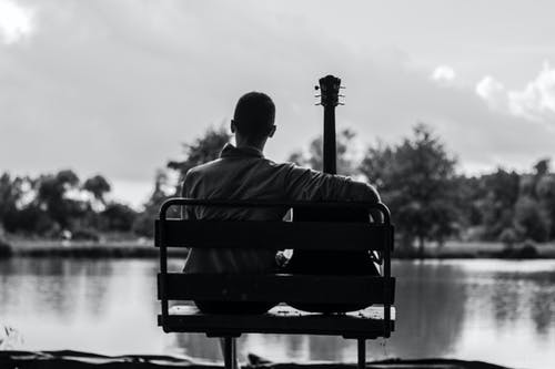 Grayscale Photo of Man Sitting Beside Guitar
