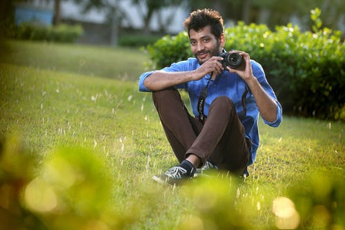 Man Sitting on Grass Holding Camera and Smiling