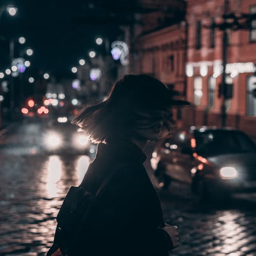 Woman in Black Jacket Carrying Backpack With Tousled Hair Walking On The Street At Night