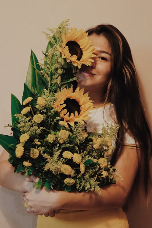 Photo of Smiling Woman Carrying Sunflower Arrangement