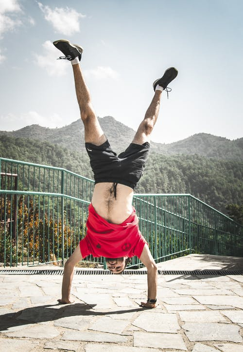 Man Doing Hand Stand on Pavement