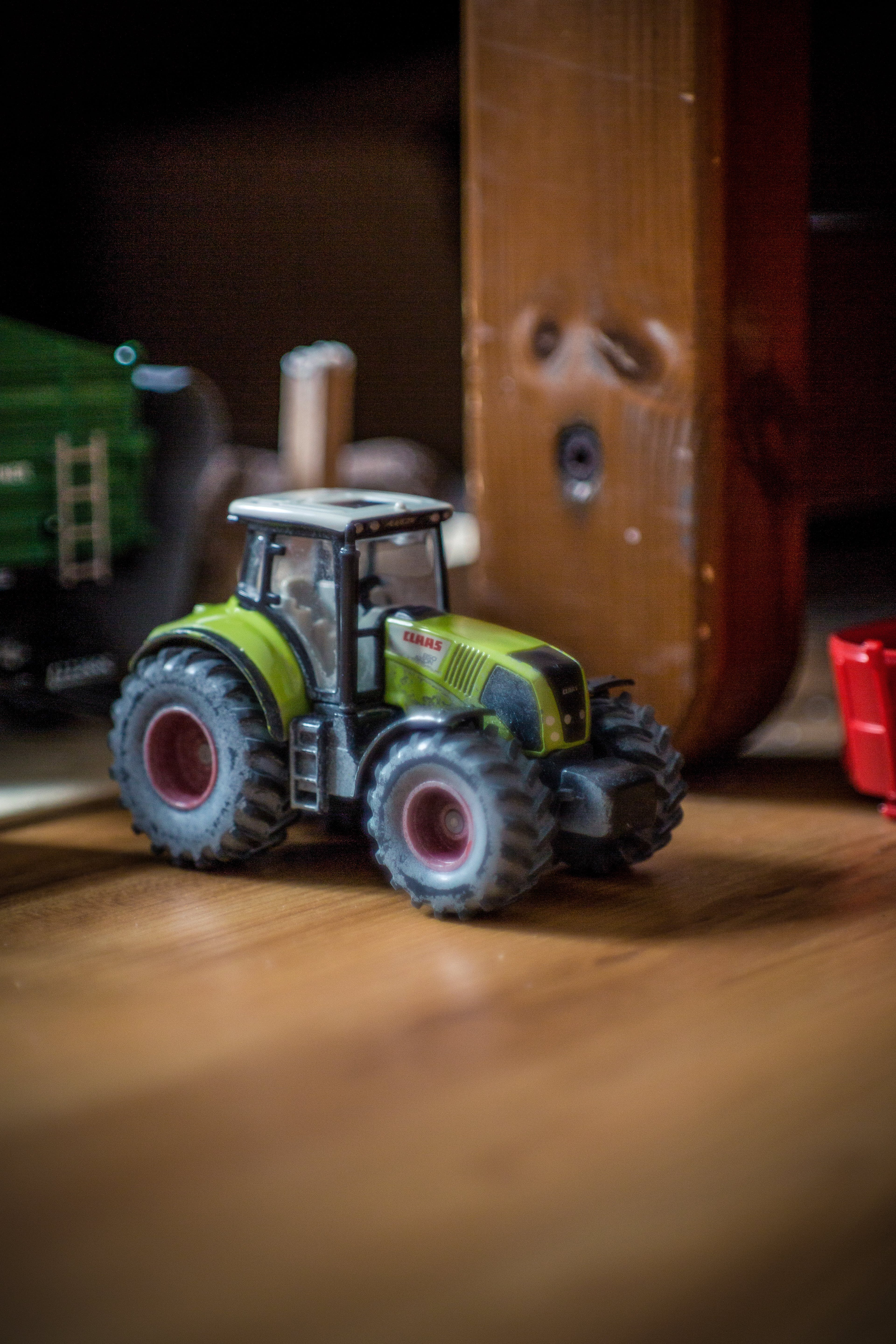 Green and Gray Tractor Plastic Model Above Wooden Surface