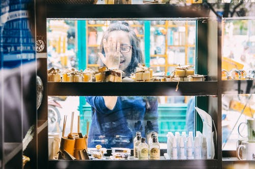 Woman Standing Beside Clear Glass Display Counter