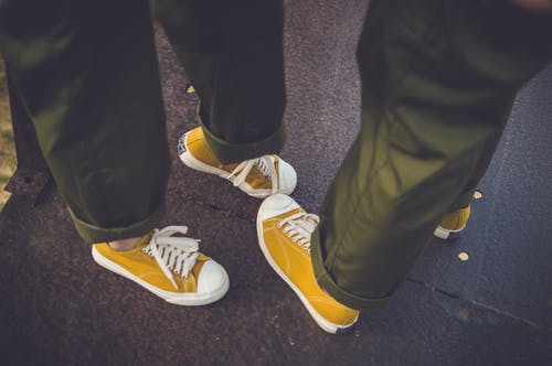 Two People Wearing Yellow-and-white Low-top Chucks