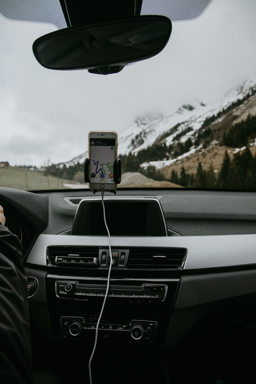 White Smartphone Docked on Car Windshield