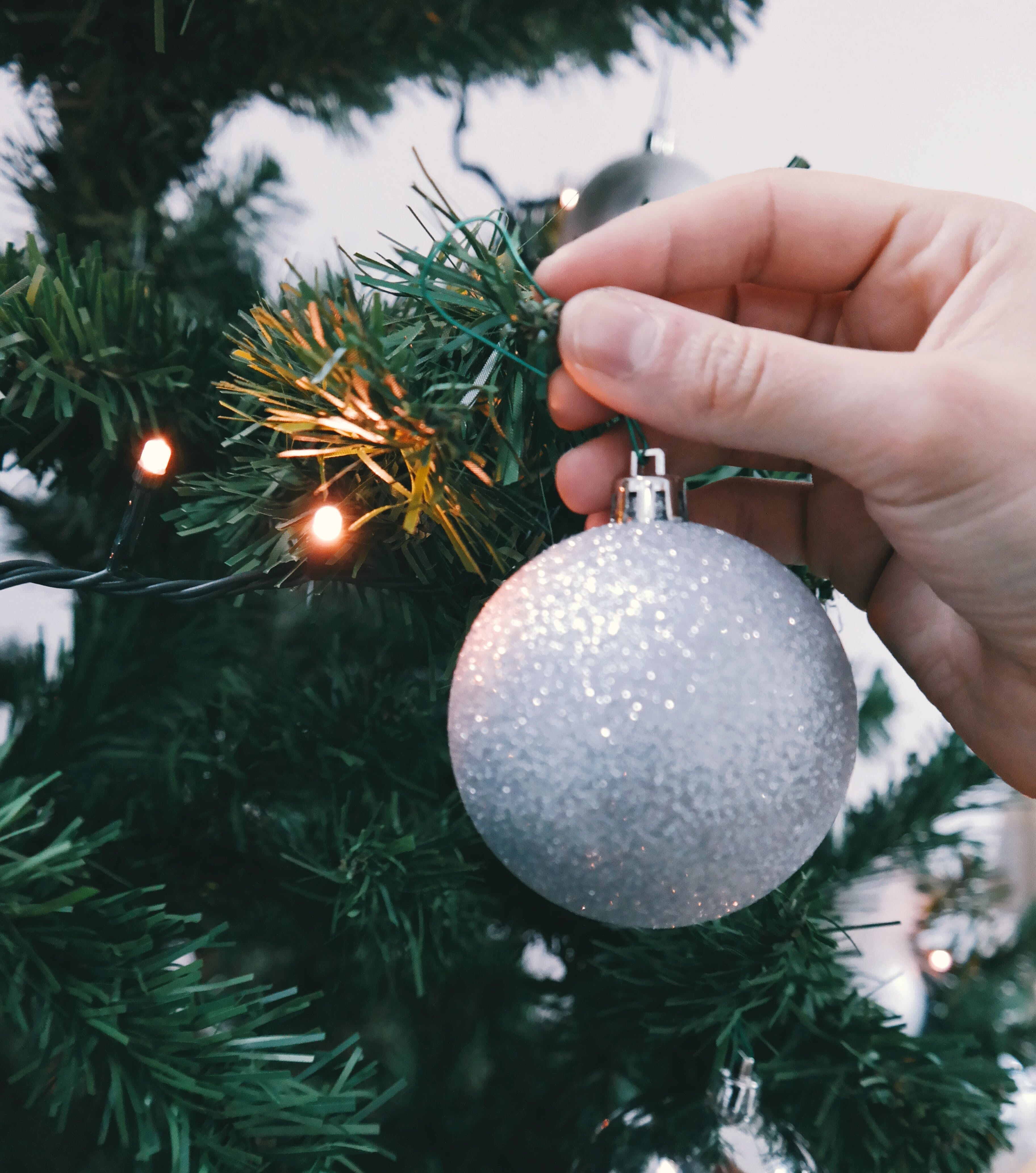 Person Holding Silver Glittered Bauble