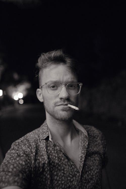Monochrome Photo of Man Smoking Cigarette